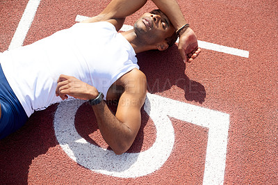 Buy stock photo Shot of a male sprinter lying down and resting on the track