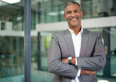 Buy stock photo Portrait of a handsome mature businessman posing with his arms folded in his office