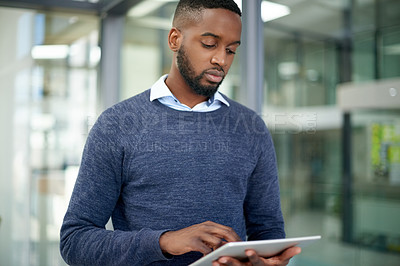 Buy stock photo Shot of a handsome young businessman using a digital tablet in his office at work