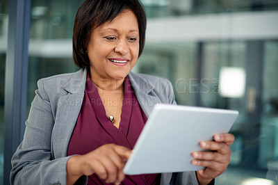 Buy stock photo Shot of an attractive mature businesswoman using a digital tablet inside her office at work