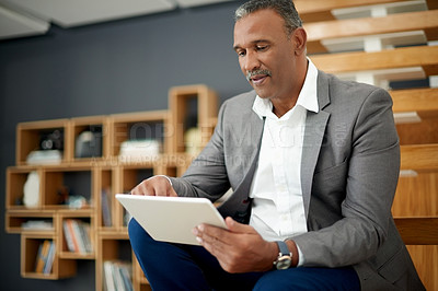 Buy stock photo Shot of a handsome mature businessman using a digital tablet in his office