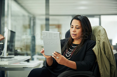 Buy stock photo Cropped shot of an attractive mature businesswoman sitting and using a tablet while in the office during the day