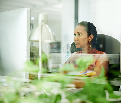 Buy stock photo Cropped shot of an attractive young businesswoman sitting and using a computer while in the office during the day