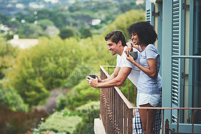 Buy stock photo Shot of an affectionate young couple drinking coffee and looking at the view while standing on a balcony at home