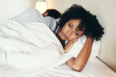 Buy stock photo Shot of an attractive young woman lying with her back turned on her husband after an argument in their bedroom