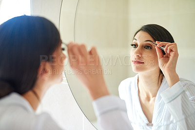 Buy stock photo Cropped shot of an attractive young woman tweezing her eyebrows in the bathroom mirror