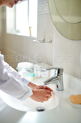Buy stock photo Cropped shot of an unrecognizable woman washing her hands in the bathroom at home