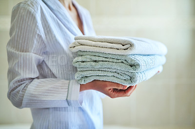 Buy stock photo Closeup shot of an unrecognizable woman carrying a pile of towels at home
