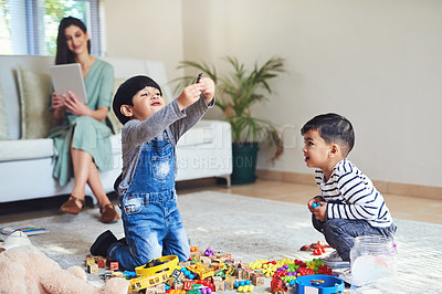Buy stock photo Shot of two young boys playing together while their mother sits in the background