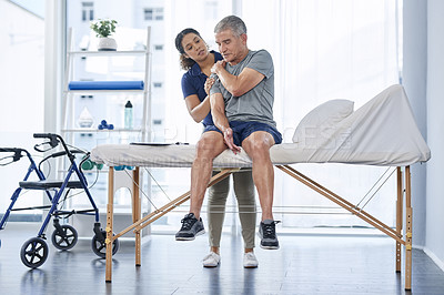 Buy stock photo Full length shot of a senior man experiencing shoulder pain while exercising with his physiotherapist at a hospital