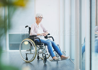 Buy stock photo Full length shot of a contemplative senior woman sitting in a wheelchair while looking away in a nursing home