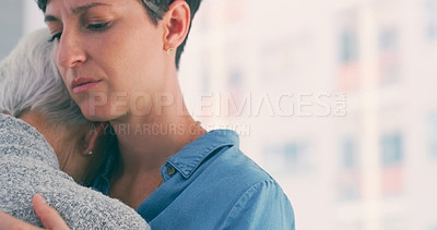 Buy stock photo Cropped shot of an attractive young woman hugging her senior mother closely while at home