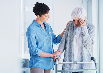 Buy stock photo Cropped shot of an affectionate young woman helping her senior mother who is suffering from a headache while at home