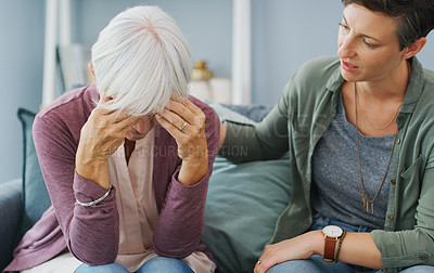 Buy stock photo Cropped shot of an attractive young woman sitting and comforting her senior mother while she suffers from a headache