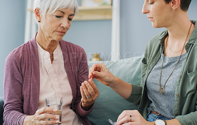 Buy stock photo Cropped shot of an attractive young woman giving her sick senior mother painkillers while sitting with her on the sofa