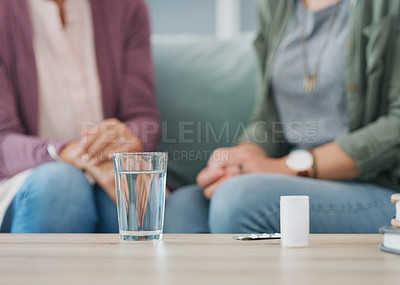 Buy stock photo Cropped shot of two unrecognizable women sitting on the sofa with a pillbox and water in the living room