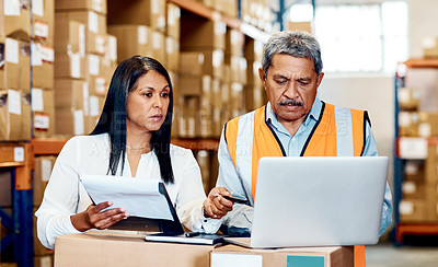 Buy stock photo Shot of a mature man and woman going through paperwork while using a laptop in a warehouse