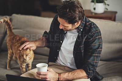 Buy stock photo Shot of a handsome young man playing with his cat while enjoying the day at home