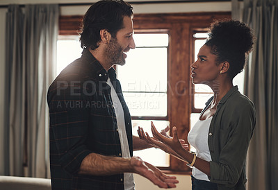 Buy stock photo Shot of a young couple having an intense argument at home