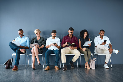 Buy stock photo Studio shot of a group of businesspeople occupying themselves while sitting in line against a grey background