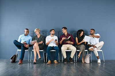 Buy stock photo Studio shot of a group of businesspeople having discussions while sitting in line against a grey background