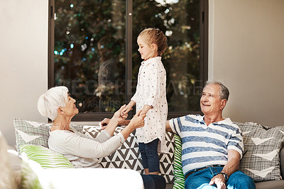 Buy stock photo Shot of an adorable little girl spending quality time with her grandmother and grandfather outside at home