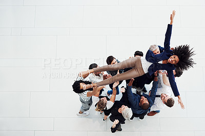 Buy stock photo High angle shot of a group of businesspeople carrying a colleague up in the air in celebration