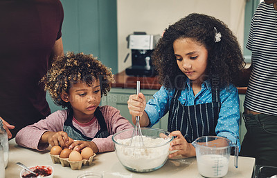 Buy stock photo Cropped shot of a young couple baking at home with their two children