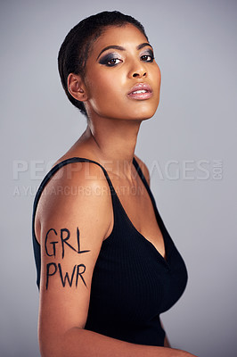 """Buy stock photo Studio shot of a young woman with """"grl pwr"""" painted on her arm posing against a grey background"""