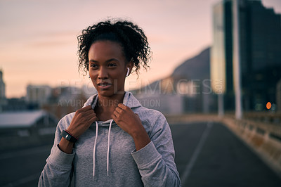 Buy stock photo Cropped shot of an attractive young woman wearing earphones while standing outside in the city before her morning run