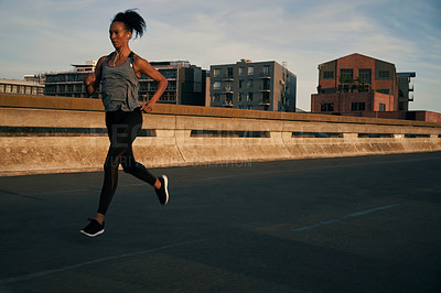 Buy stock photo Full length shot of an attractive young woman wearing earphones and running while outdoors in the city during sunrise