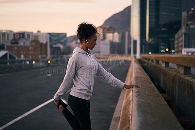 Buy stock photo Cropped shot of an attractive young woman stretching alone before going for a morning run outside in the city