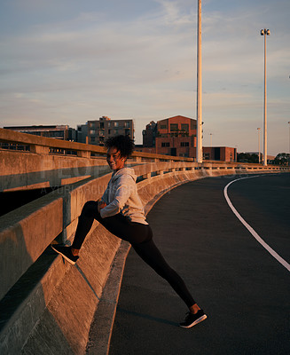 Buy stock photo Full length portrait of an attractive young woman stretching alone before going for a morning run outside in the city