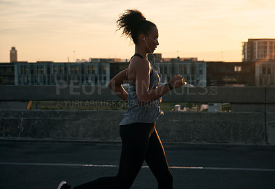 Buy stock photo Cropped shot of an attractive young woman wearing earphones while running outside in the city during the morning