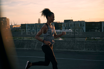 Buy stock photo Cropped shot of an attractive young woman wearing earphones and running while outside in the city during the morning