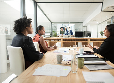 Buy stock photo Shot of a group of young businesswomen having a video conference in a modern office