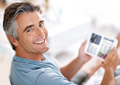 Buy stock photo Cropped portrait of a handsome mature man using a tablet while sitting on his living room sofa