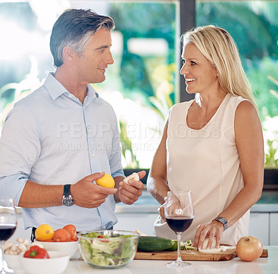 Buy stock photo Cropped shot of an affectionate mature couple talking while making dinner together