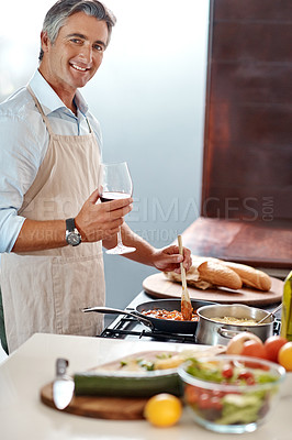 Buy stock photo Cropped portrait of a handsome mature man cooking dinner in his kitchen at home
