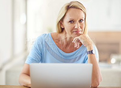 Buy stock photo Cropped portrait of an attractive mature woman sitting and using a laptop while in her living room during the day