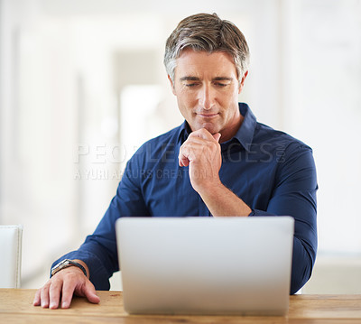 Buy stock photo Cropped shot of a handsome mature man sitting and using a laptop while in his living room during the day