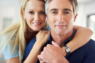 Buy stock photo Cropped portrait of a happy mature couple hugging each other while in the living room during the day