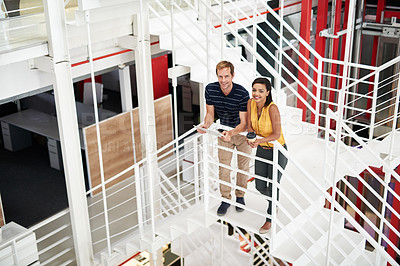 Buy stock photo High angle portrait of two business colleagues standing together on a flight of stairs in the office