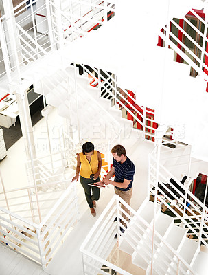 Buy stock photo High angle shot of two business colleagues standing together on a flight of stairs in the office