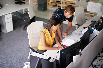 Buy stock photo Cropped shot of two business colleagues working together in their office