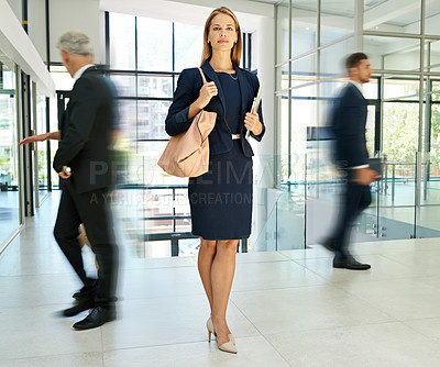 Buy stock photo Full length shot of an attractive young businesswoman standing in a modern office while her colleagues walk around her