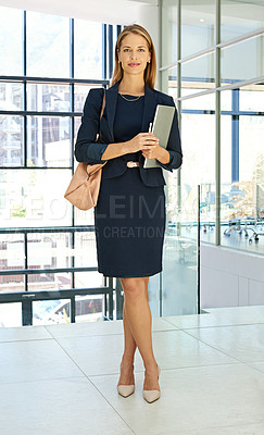 Buy stock photo Full length portrait of an attractive young businesswoman standing alone in a modern office and holding a tablet