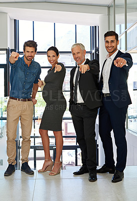 Buy stock photo Full length portrait of a diverse group of businesspeople standing together in a modern office and pointing