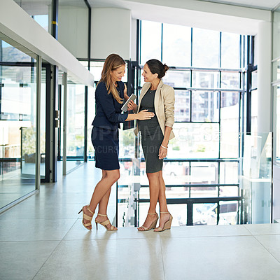 Buy stock photo Full length shot of an attractive young businesswoman rubbing her attractive young coworker's pregnant stomach while in a modern office