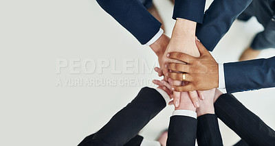 Buy stock photo High angle shot of a group of unrecognizable businesspeople standing in a huddle with their hands stacked together